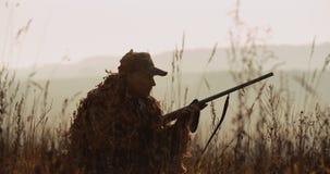 De jager in de jachtmateriaal ligt in wachttijd in zonsonderganglicht, zag het doel en het doel met geschoten kanon mistig landsc stock videobeelden