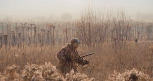 De jager in de jachtmateriaal met een geweer in zijn hand neemt door de struik op het gebied heimelijk Zonsopgang licht en mistig stock video
