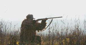 De jager ligt in wachttijd op het gebied Een mens in de jachtmateriaal in zonsonderganglicht vindt het doel en het doel met gewee stock video