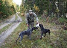 De jager neemt prooi van twee jachthonden stock afbeelding