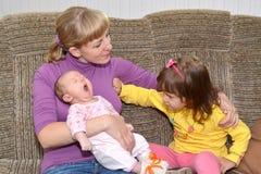 De jaloersheid van kinderen Het drie-jaar-oude meisje duwt weg motherahand, bekijkend de kleine zuster Royalty-vrije Stock Fotografie