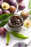 De jam van de pruim in een glaskruik en verse vruchten met leav Stock Afbeeldingen