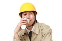 De Japanse bouwvakker neemt een koffiepauze Stock Foto