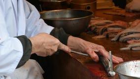 De Japanse mensen doden en fileren palingsvissen voor tonen en het koken kabayaki of palingsgrill met zoete saus