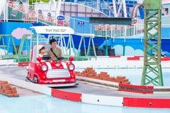 De Japanse papa en zijn dochter genieten van hun tijd samen berijdend o Royalty-vrije Stock Afbeeldingen