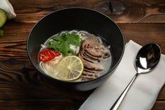 De Japanse soep van phobo in een zwarte plaat op houten achtergrond stock fotografie