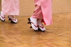 De Japanse vrouwen die in traditioanl kleden zich en geta schoenen dansen stock afbeelding