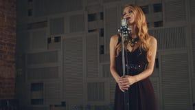 De jazzvocalist in elegante kleding presteert op stadium bij microfoon Donkere pommade stock videobeelden