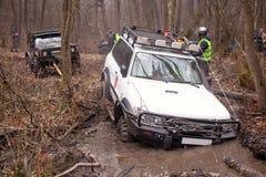 De jeep trekt de auto uit de modder Royalty-vrije Stock Afbeeldingen