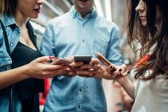 De jeugd die van de telefoonverslaafde gadgets in metro gebruiken stock fotografie