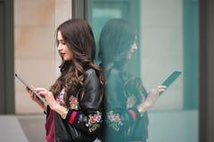 De jeugd en technologie Aantrekkelijke jonge vrouw die tabletcomputer in openlucht met behulp van stock fotografie