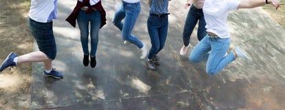 De jeugd in Jeans en en Keds die lopen springen stock foto's