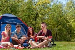 De jeugd op kamperen die een grote tijd hebben Stock Foto