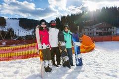 De jeugd in skikostuums en skibeschermende brillen die zich met snowboards bevinden royalty-vrije stock afbeelding