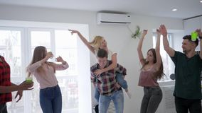 De jeugd voor de gek houdt rond bij een huispartij, dansen de jongens en de meisjes en hebben pret in keuken met plastic binnen g stock footage