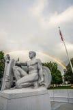 De jeugd Zegevierend onder dubbele regenboog stock foto