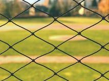 De jeugdhonkbalveld van achter netto wordt bekeken die royalty-vrije stock foto's