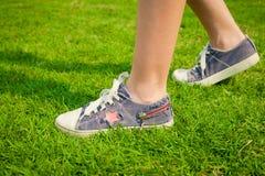 De jeugdtennisschoenen op meisjesbenen op gras Royalty-vrije Stock Afbeelding
