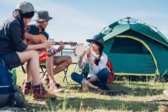 De jeugdvrienden samen en grappige speelmuziek die kamperen stock afbeeldingen