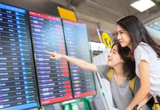 De jeune fille d'Asiatique voyageur ensemble regardant l'horaire Photos libres de droits