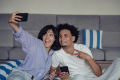 De jeunes couples de sourire prenant des selfies dans le lit utilisant un smartphone, ils se couchent et pose images libres de droits