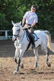 De jockey in glazen met ranselt het berijden paard Stock Foto's