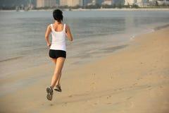 De jogging van de geschiktheidsvrouw bij zonsopgang/zonsondergangstrand Royalty-vrije Stock Foto