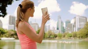 De jogging van de vrouwenagent in park Geschikte vrouwelijke sportfitness opleiding Het spreken met vriend via Skype stock videobeelden