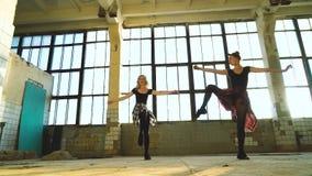 De jolies danseuses font des exercices pour les jambes dans l'ancienne usine clips vidéos