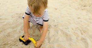 De jong geitje speel raod werken met stuk speelgoed excavatorin in zand stock footage