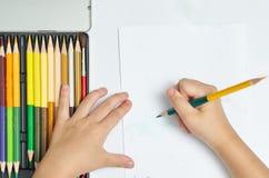 De jong geitjehanden houdt kleurenpotlood en denken over tekeningsdingen op w royalty-vrije stock afbeeldingen