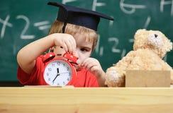De jong geitjejongen in academisch GLB dichtbij microscoop, houdt klok in klaslokaal, bord op achtergrond Het kind op droevig gez Stock Afbeelding