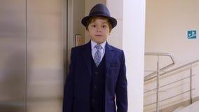 De jong geitjejongen kijkt als een zakenman in kostuum en de hoed wacht lift in zijn bureau Het levensparodie van de volwassene stock video
