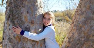 De jong geitjemeisjes houdt aard van omhelzing een boom tunk royalty-vrije stock afbeeldingen