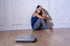 De jonge aan anorexie lijdende zitting van de tienervrouw alleen op grond die de schaal bekijken maakte zich en drukte in het op  stock afbeeldingen