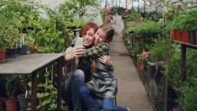 De jonge aantrekkelijke arbeider van serre en haar leuk emotioneel kind nemen selfie het koesteren van het kussen en het stellen  stock videobeelden