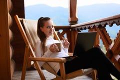 De jonge aantrekkelijke bedrijfsvrouw werkt aan laptop bij bergtoevlucht met een kop thee en een koekje Het wijfje ontspant Royalty-vrije Stock Afbeeldingen