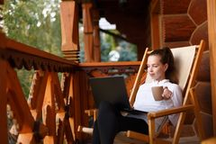 De jonge aantrekkelijke bedrijfsvrouw werkt aan laptop bij bergtoevlucht met een kop thee en een koekje Het wijfje ontspant Stock Foto's