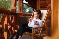 De jonge aantrekkelijke bedrijfsvrouw werkt aan laptop bij bergtoevlucht met een kop thee en een koekje Het wijfje ontspant Stock Fotografie