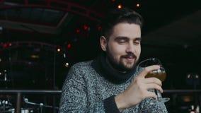 De jonge aantrekkelijke blauw-eyed gebaarde mens in een warme sweater drinkt bier, is verrast met de smaak, kijkt net naar stock videobeelden