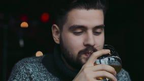 De jonge aantrekkelijke blauw-eyed gebaarde mens in een warme sweater drinkt bier, is verrast met de smaak, kijkt net naar stock footage