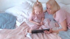 De jonge aantrekkelijke blonde vrouw die een boek op tablet haar lezen weinig charmante dochter in roze kleedt het leggen op bed stock footage