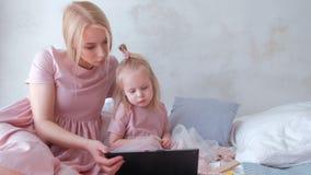 De jonge aantrekkelijke blonde vrouw met haar weinig charmante dochter in roze kleedt het letten op video in tablet stock video