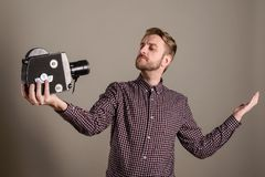 De jonge aantrekkelijke cameraman in een plaidoverhemd neemt zich weg aan een oude filmcamera Selfficoncept stock foto's