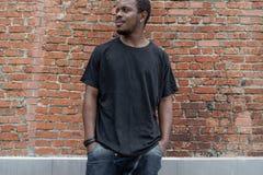 De jonge aantrekkelijke donker-gevilde mens in zwarte T-shirt op rood bricked achtergrond royalty-vrije stock fotografie