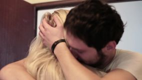 De jonge aantrekkelijke donkere haired mens gaat flat in en koestert blonde bij deuropening stock video