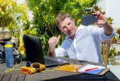 De jonge aantrekkelijke en gelukkige digitale nomademens die in openlucht van koffiewinkel werken met laptop computer die selfie  stock fotografie