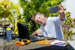 De jonge aantrekkelijke en gelukkige digitale nomademens die in openlucht van koffiewinkel werken met laptop computer die selfie  royalty-vrije stock afbeeldingen