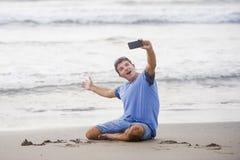 De jonge aantrekkelijke en gelukkige Kaukasische jaren '30mens die pret hebben bij Aziatisch strand die selfie stelt met mobiele  stock foto