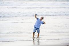 De jonge aantrekkelijke en gelukkige Kaukasische jaren '30mens die pret hebben bij Aziatisch strand die selfie stelt met mobiele  stock fotografie